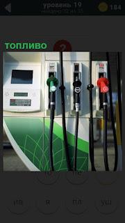 На заправочной станции показано топливо и пистолеты разного цвета