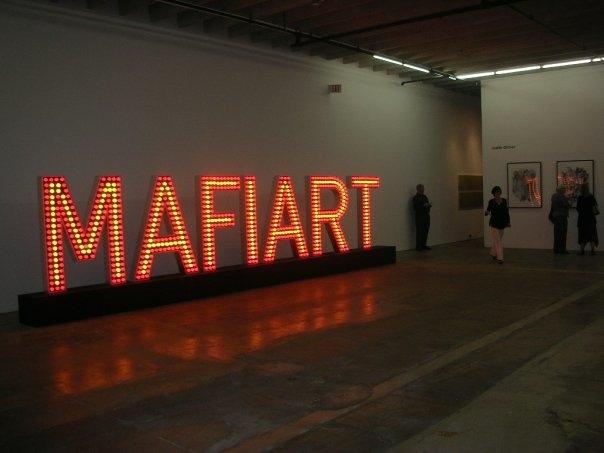 """MAFIART - 2009 - Wood,metal, 852 Red and yellow flashing light bulbs 24' X 24"""" X 6'4""""(L X W X H) or 12 m x 2,20 m Mafiart is a word creates by Klaus Guingand in 1993. Mafiart TM © Klaus Guingand"""