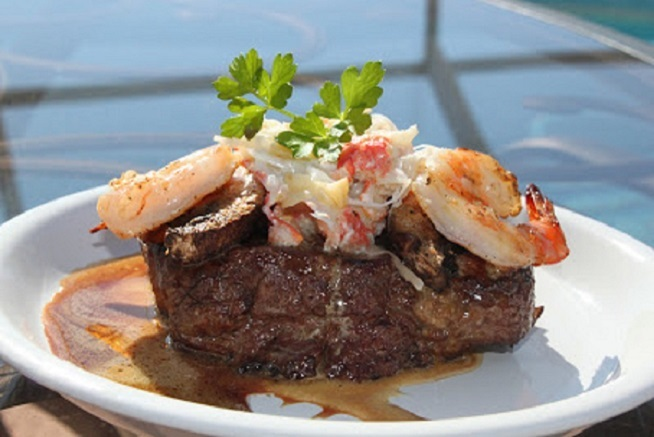 this is a filet mignon with crab and shrimp on top on a white plate