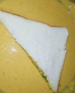 Dipping triangular shape bread pakora into the batter