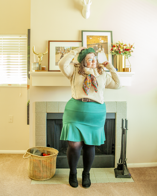 An outfit consisting of a forest green beret, a cowl neck sweater belted over a green fitted dress and black boots.