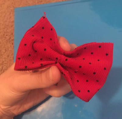 A picture of a piece of red fabric being folded into a bow, using an accordion style fold