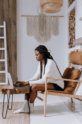 white room with retro furniture and black woman on laptop