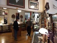 2 men talking in room full of historic items