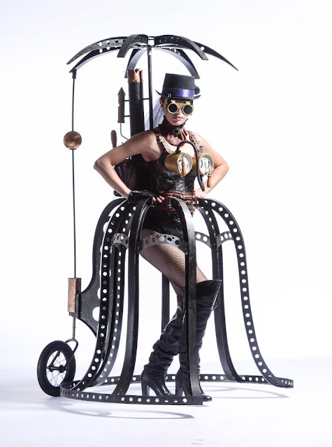 Steampunk Cage Skirt Costume for Halloween or cosplay. Steel cage skirt with penny farthing wheel, steel parasol, steam gauge bra, steam powered backpack, boots, goggles and hat. Steampunk concept clothing for women.