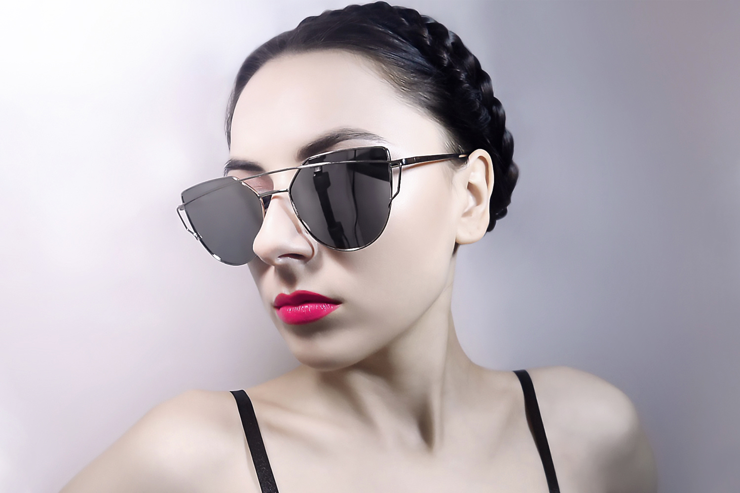 woman on a plain background with updo hairstyle is wearing and oversized mirrored, aviator sunglasses