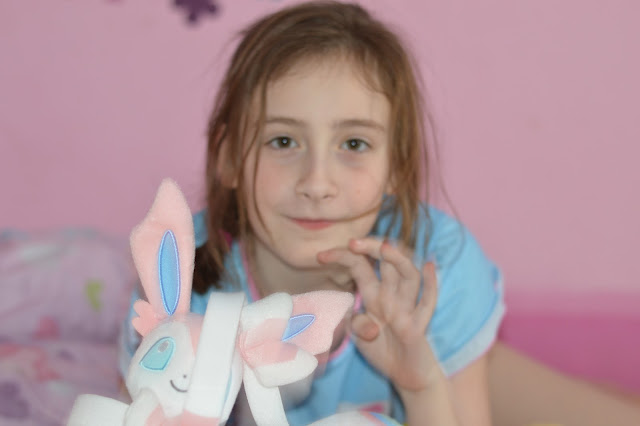 Sasha holding Sylveon toy