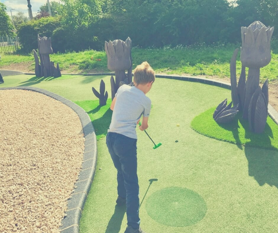 A young boy hits a golf ball, his back is to the camera.