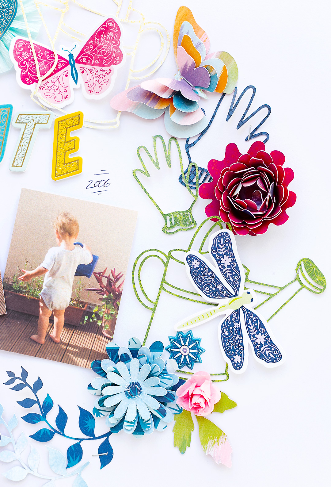 Watering Can, butterfly, leaves and pretty flowers on a scrapbook layout