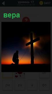 Человек склонив колено молится около креста в вечернее время, когда солнце почти скрылось за горизонт