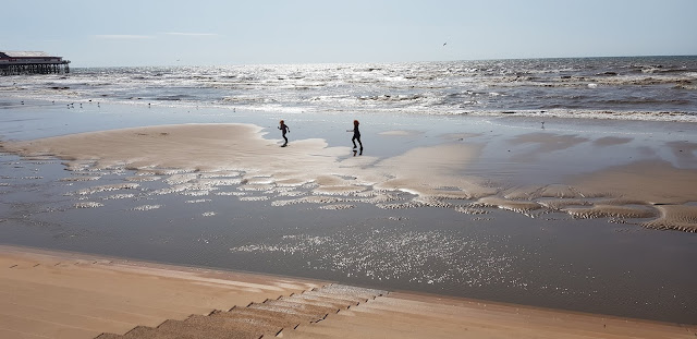 Blackpool beach two boys running along the sand banks with very shallow water around