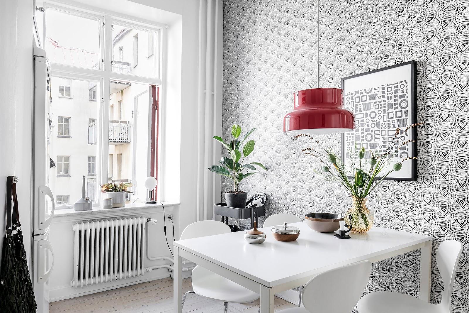 White kitchen design inside of a small scandinavian interior, pattern wallpaper, red retro lamp