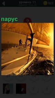 На яхте по морю под парусом следует мужчина на корме, управляя судном