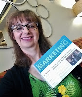 headshot of Kathy Dempsey holding a copy of Marketing Library Services newsletter