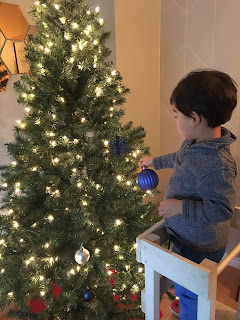 crianca decorando arvore de natal