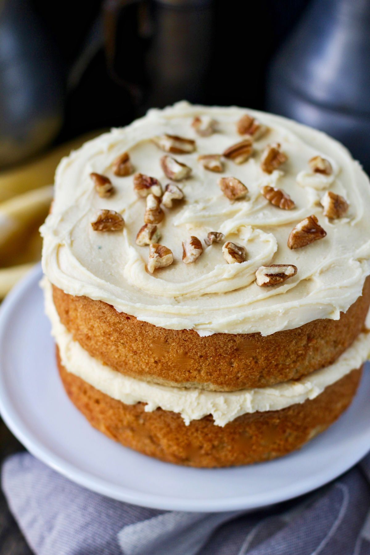 Maple cake on a cake stand with pecans.