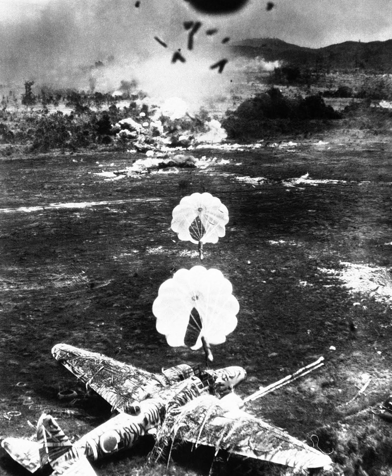 Para-frag bombs fall toward a camouflaged Japanese Mitsubishi Ki-21,