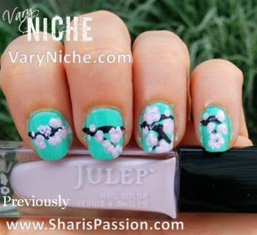 Fingernails with pale pink & mauve flowers dotted over a dark brown branch running across nails with a teal background.