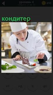 На кухне кондитер за приготовлением своего блюда, последний штрих зеленью украшает