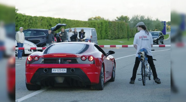 Uma Ferrari corre contra uma bicicleta
