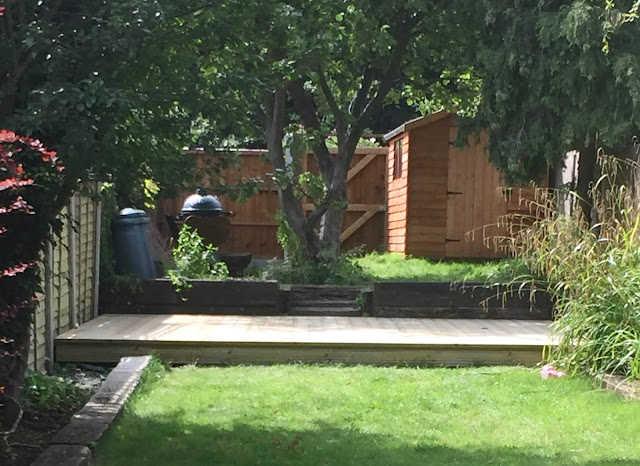 My garden with grass, decking, railway sleepers, a shed, compost bin and big green egg