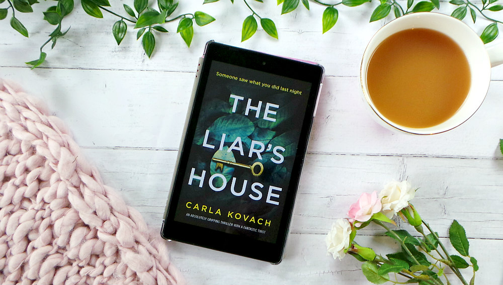 Kindle fire screen showing the cover for the Liars House. The cover has a gold key on a pile of leaves. The background of the image features some leaves, roses, cup of tea and a pink chunky knit blanket