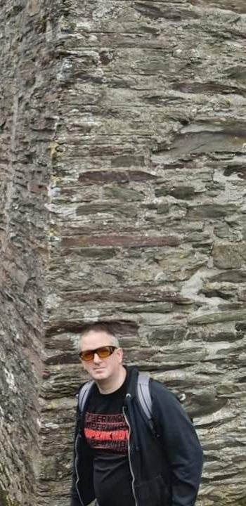 Picture of Damon Lord in front of a wall, wearing shades and a Superknova t-shirt