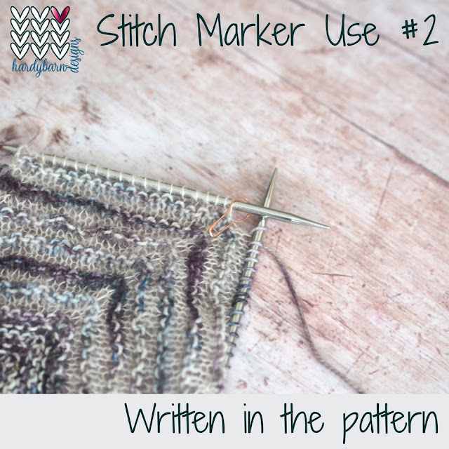 Grey and purple knitting on needles with stitch marker