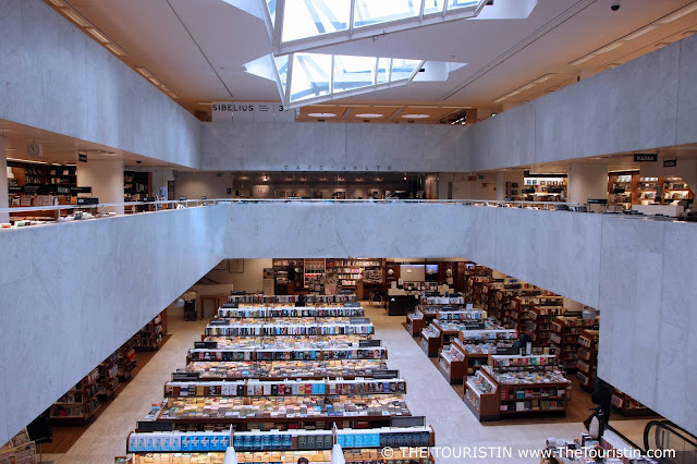 Two levels of books on shelves with an artistic skylight in the ceiling