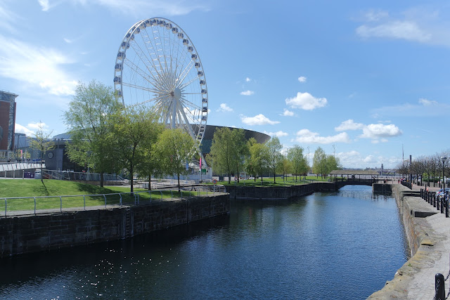 a photograph of the liverpool wheel on a sunny day with blue skies