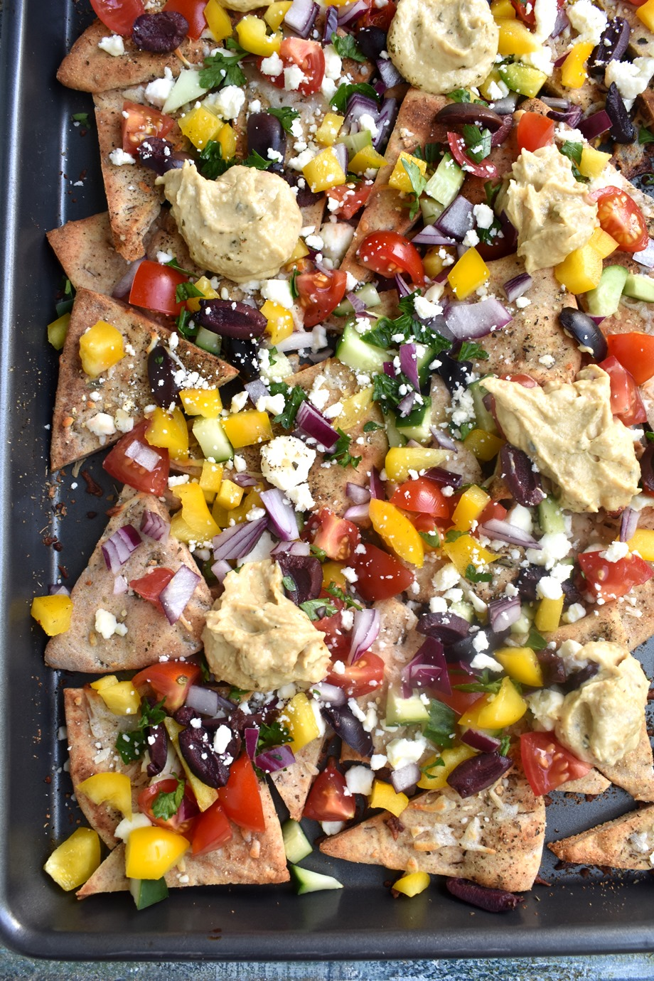 Loaded Greek Nachos are loaded with melted mozzarella and feta cheeses, creamy hummus, tomato, cucumber, olives and more for a flavor-packed, crowd pleasing appetizer!