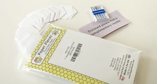 An open package of paper hexagon templates with some templates spilling out in an arc, next to a machine sewing needle on a white background.