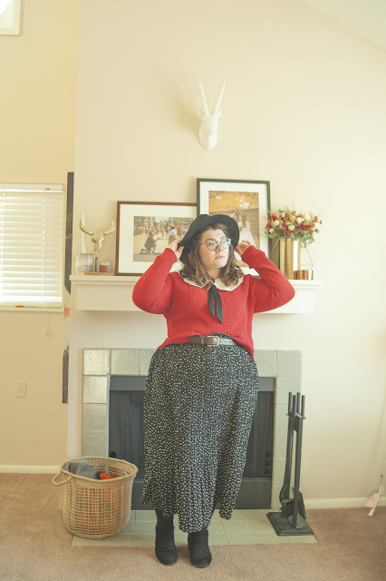 An outfit consisting of a wide brim hat, an oversized white collar, a black ribbon tied into a bow under the collar, a red sweater half tucked into a black and white micro dot print maxi skirt and and black ankle boots.