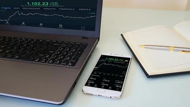 financial market integration - stock trading on mobile and laptop
