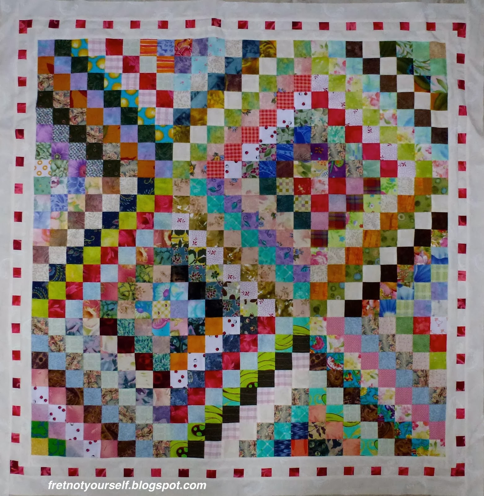A small quilt of nine Scrappy Trip blocks is bordered in pink and white.