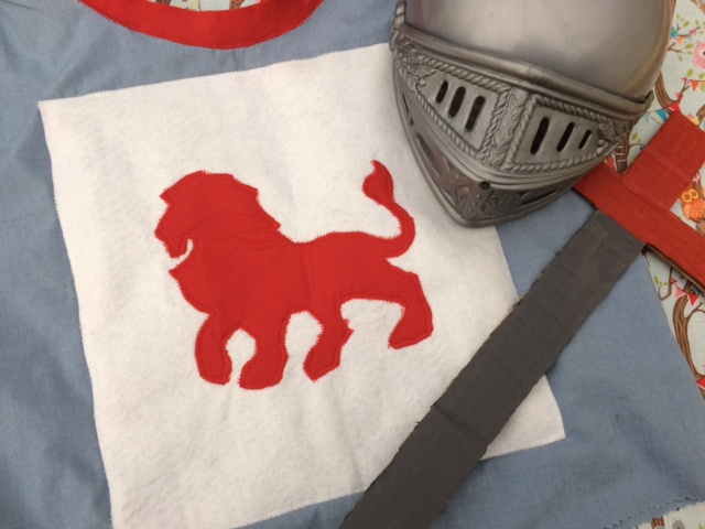 A knights tunic with a lion crest, a knights helmet and a cardboard sword