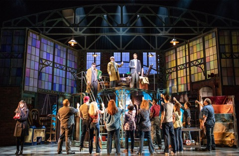 the cast of kinky boots assemble in a set designed to look like a factory, raising glasses of champagne