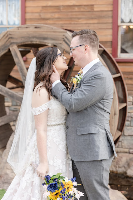 bride and groom in front of waterwheel