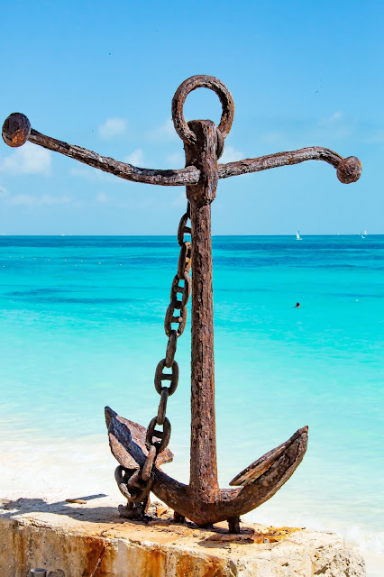 Anchor on beach with turquoise ocean behind:Photo by Lynda Hinton on Unsplash