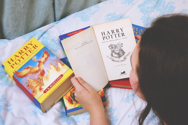 Girl looking at Harry Potter books on bed