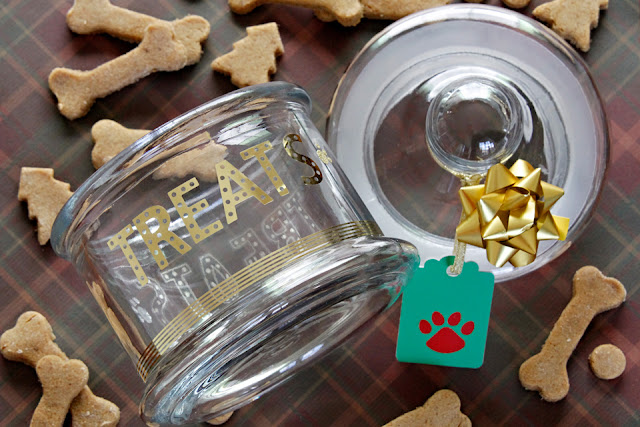 Glass dog treat jar surrounded by homemade Christmas dog treats