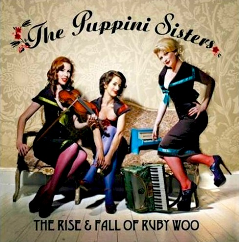 'The Rise and Fall of Ruby Woo' album cover with the singers and their instruments on an antique coach; Marcella Puppini, center, is displaying some décolletage