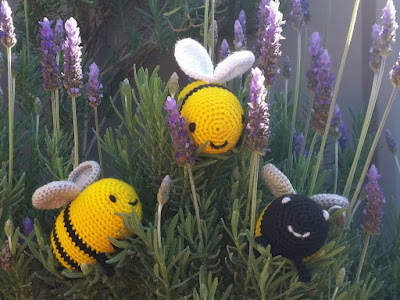 Three crocheted bees' faces poking out from between the sprigs of a lavender bush. A triangular arrangement, the top bee has a yellow face with white wings, the bottom left is sideways with a yellow face,two black stripes and silver wings, facing the top bee. Bottom right is a black-faced bee with white mouth and eyes and silver wings. Each bee is smiling.