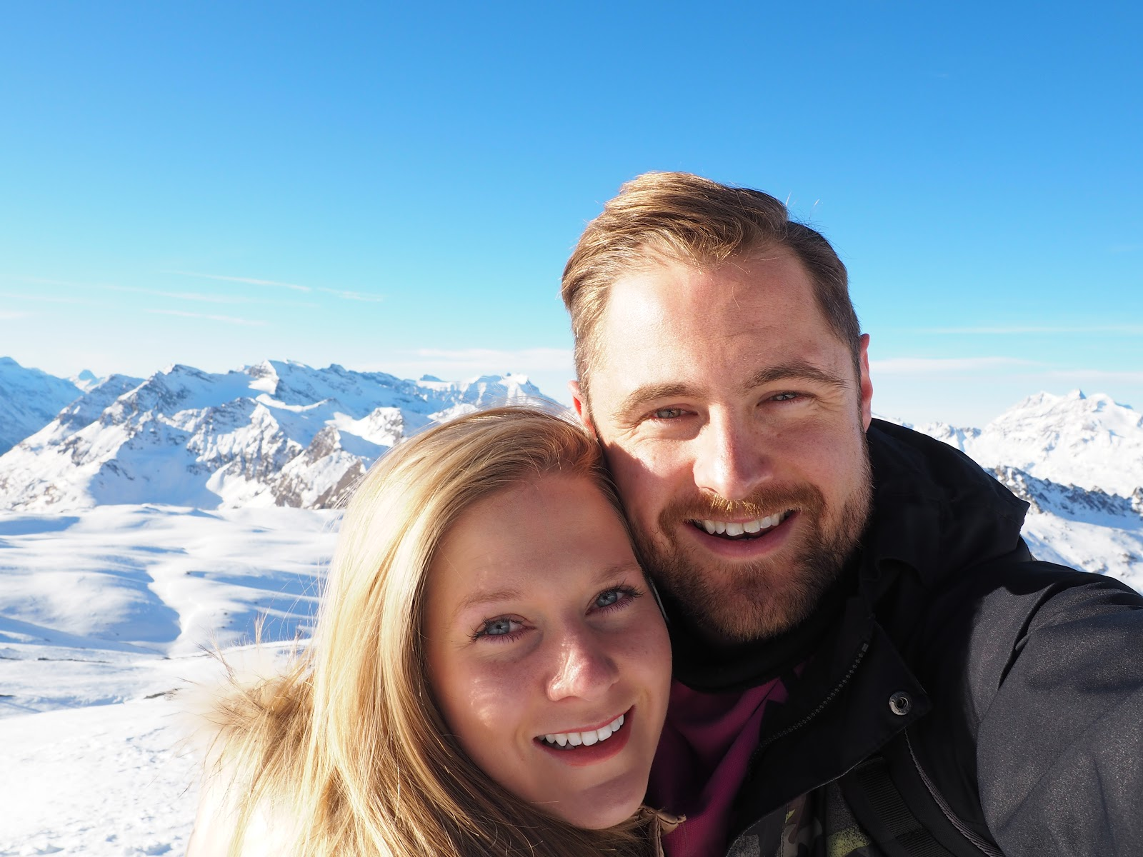 couple standing on top of a snowy mountain in Val d'isere, France