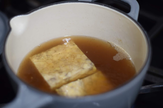 The tempeh boiling in the vegetable broth on the stove.