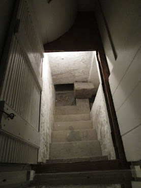 View looking down a set of stairs. There is a door to the right at the bottom.