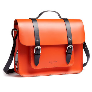 A rectangular large bright red satchel bag with black fabric straps on a bright background