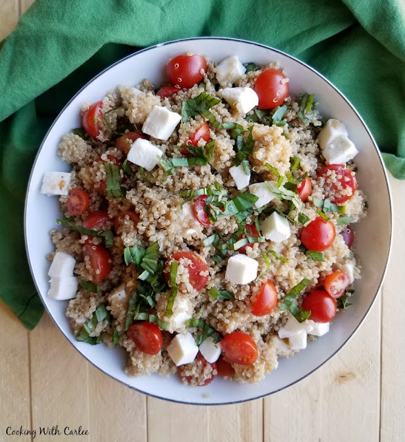 serving bowl full of quinoa, halved cherry tomatoes, cubes of mozzarella and bits of fresh basil making a caprese salad