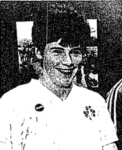 A smiling woman with short dark hair and a white football shirt