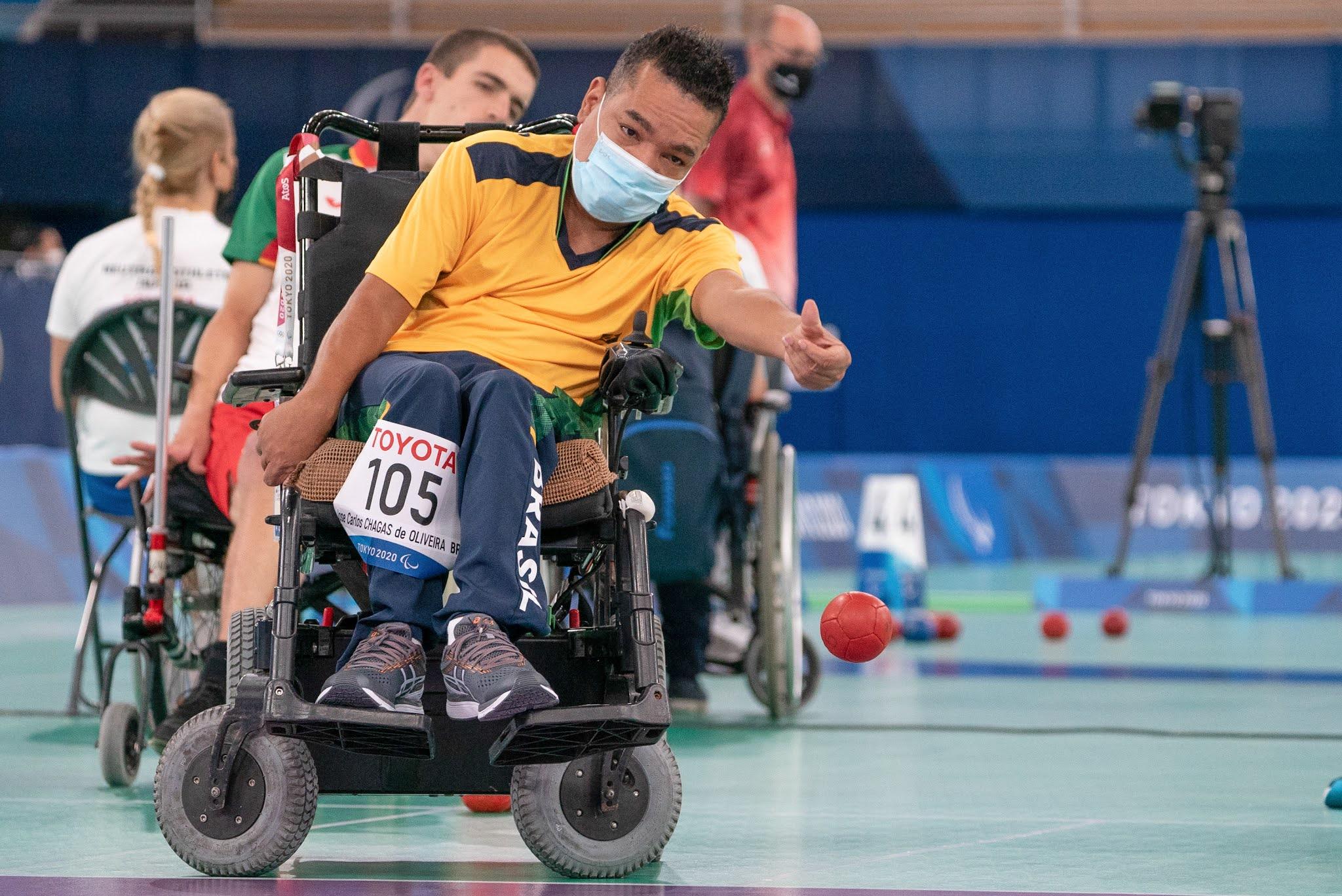 Jose Carlos Chagas, com uma cadeira de rodas motorizada, está de mascara e arremessa a bolinha